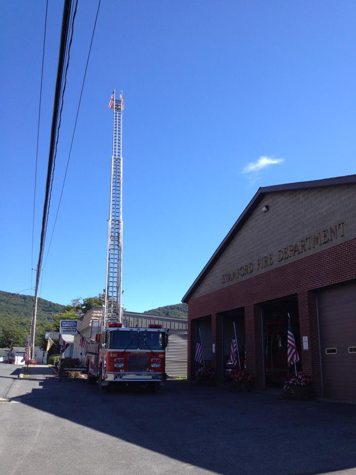 ladder truck in the front of the fire house